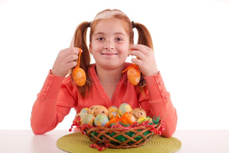 Menina ruivo pequena bonita com as tranças que guardam a Páscoa por exemplo foto de stock