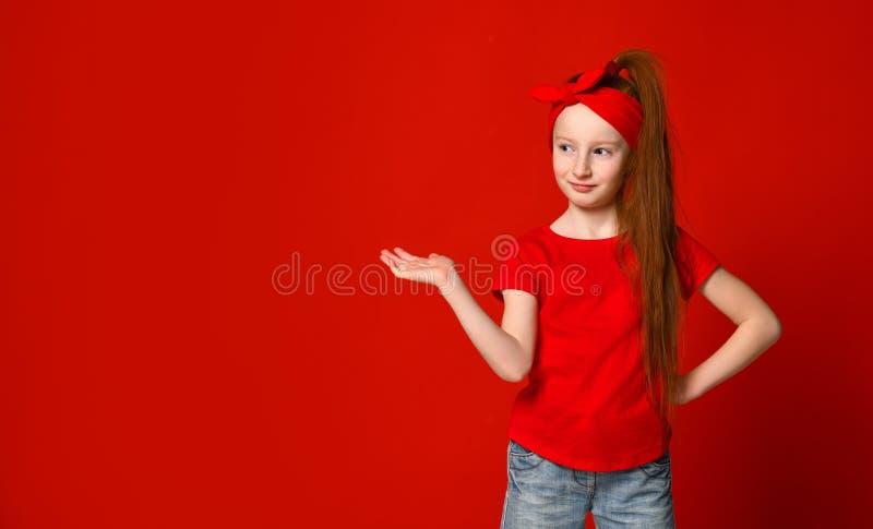 Menina ruivo pequena bonito com uma atadura em seus cabelo, sorrisos e lugares um ponto para sua propaganda imagem de stock