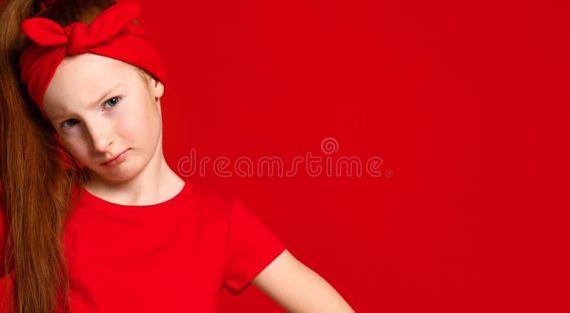 Menina ruivo pequena bonito que amua e que olha de sobrancelhas franzidas ao guardar as m?os na cintura, ofendida e decepcionada fotografia de stock royalty free