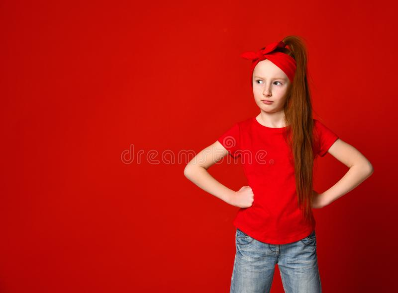 Menina ruivo pequena bonito que amua e que olha de sobrancelhas franzidas ao guardar as m?os na cintura, ofendida e decepcionada imagens de stock royalty free