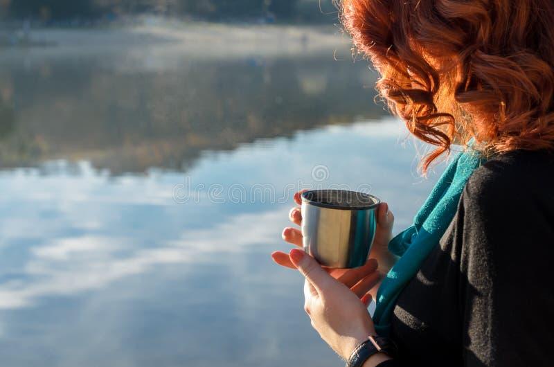menina ruivo que realiza em suas mãos um o copo da garrafa térmica imagens de stock