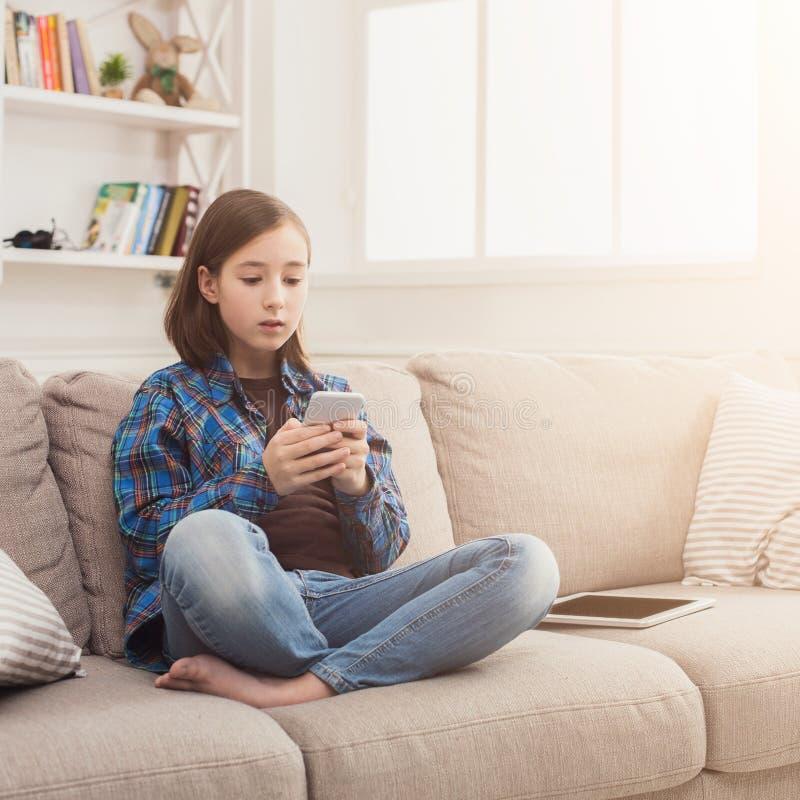 Menina séria com smartphone em casa fotografia de stock