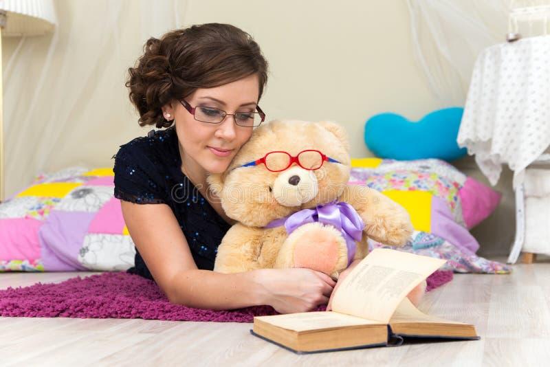 Menina séria e urso de peluche que lê um livro nos vidros fotografia de stock