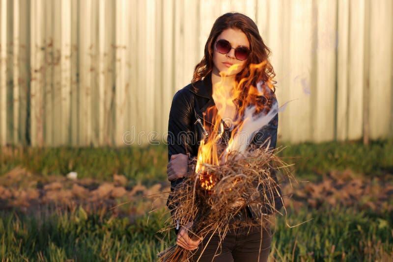 Menina séria nos óculos de sol que estão em um revestimento preto com um fogo em suas mãos fora imagem de stock royalty free