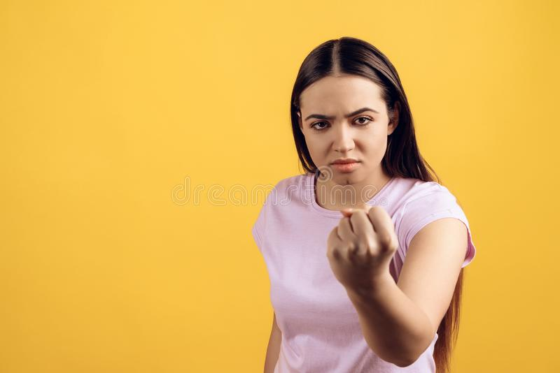A menina séria nova ameaça com o punho imagem de stock royalty free