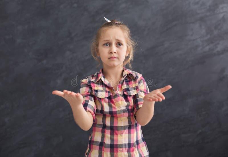 Menina séria que levanta no fundo cinzento imagem de stock royalty free