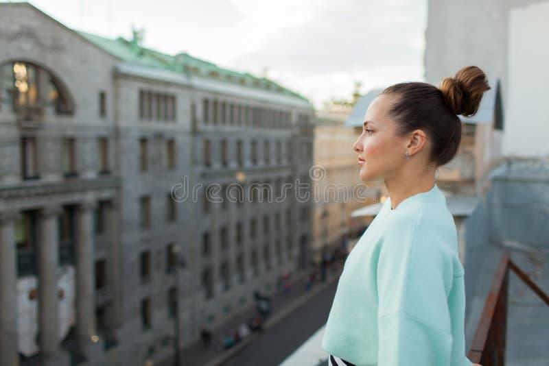 A menina só bonita está no telhado da casa na cidade e nos sonhos velhos fotos de stock royalty free