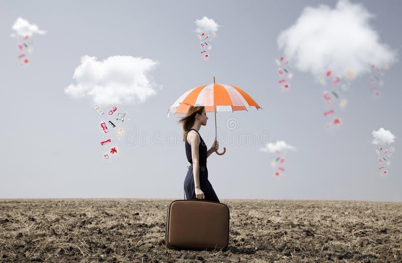 A menina só com mala de viagem e o guarda-chuva no campo colocam imagens de stock royalty free
