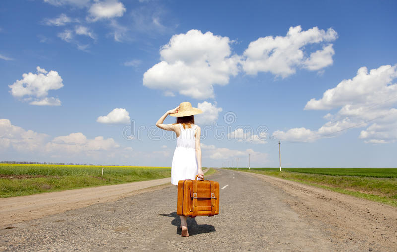 Menina só com a mala de viagem na estrada secundária. fotos de stock