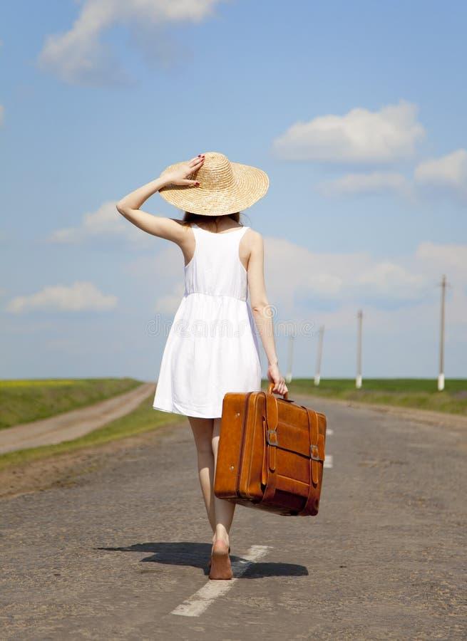 Menina só com a mala de viagem na estrada secundária. foto de stock royalty free