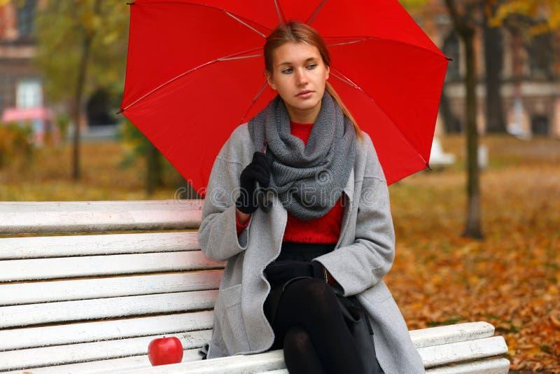 Menina só com um guarda-chuva vermelho que senta-se em um banco imagem de stock