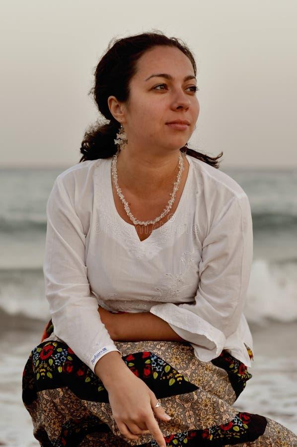 Menina só que senta-se pela ressaca do mar, brisa do verão fotografia de stock