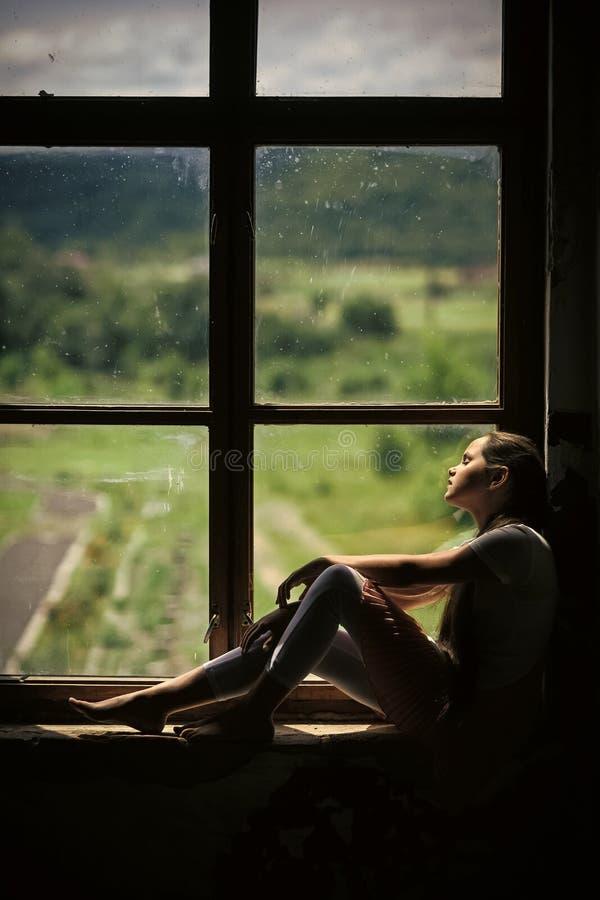 Menina só Sono da moça no peitoril da janela com opinião da paisagem do verão foto de stock