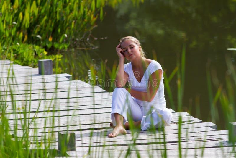 menina 20s loura que relaxa e que sonha acordado perto da água foto de stock
