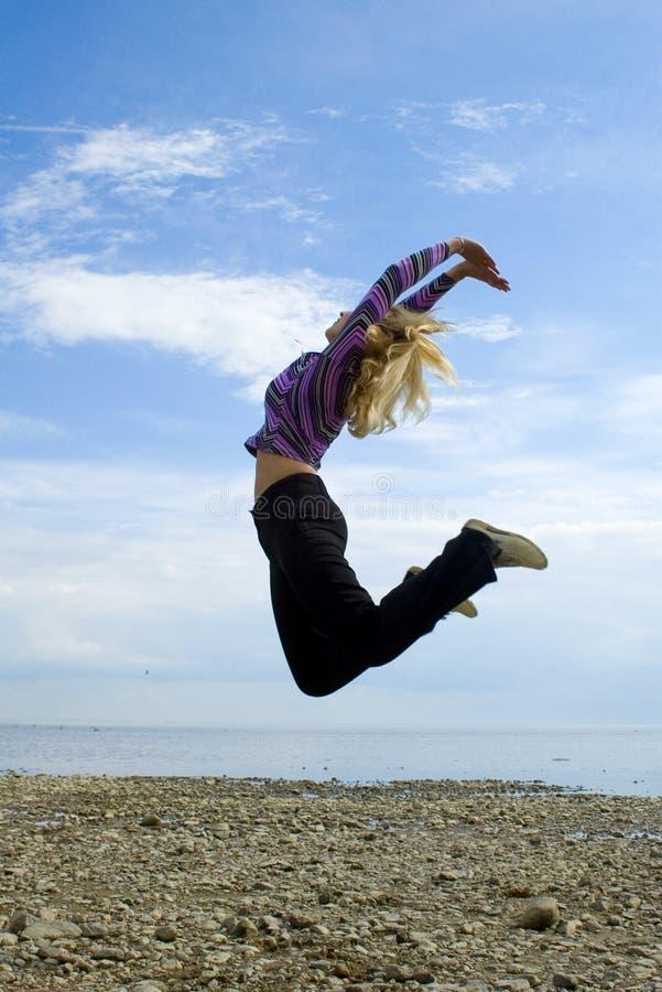A menina salta acima do mar Báltico fotos de stock royalty free