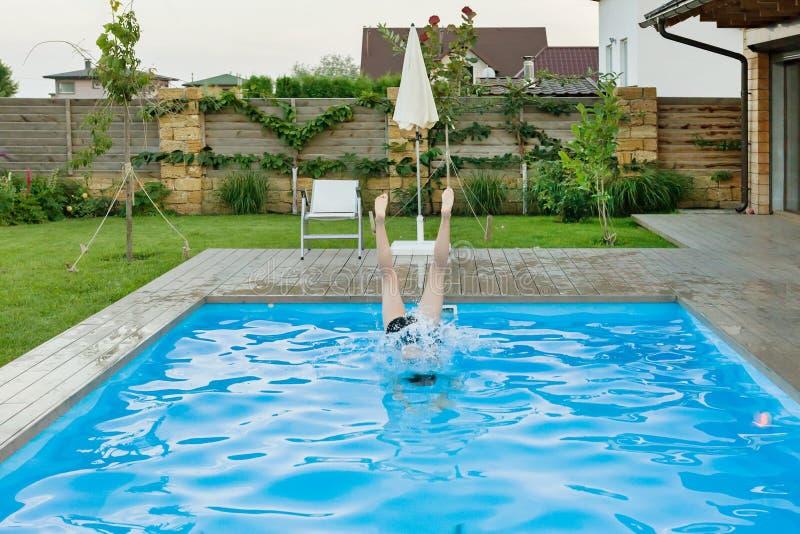 A menina salta na associação, mostras da foto os pés que colam acima fora da água fotografia de stock royalty free