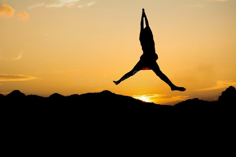 A menina salta no céu sob a luz do por do sol imagens de stock