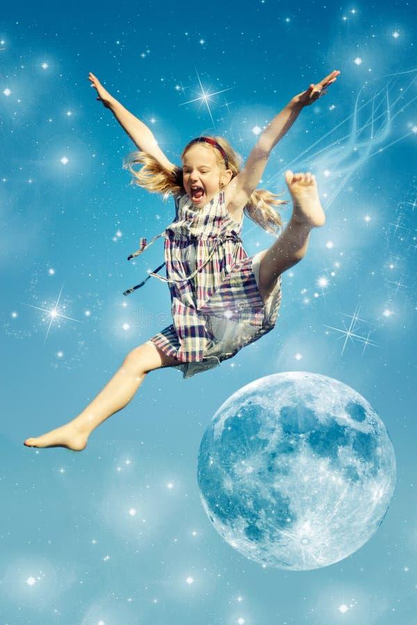 A menina salta sobre a lua fotos de stock royalty free