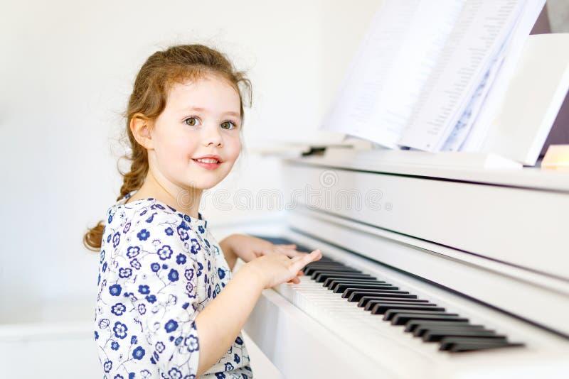 Menina saudável bonito da criança que joga o piano na sala de visitas ou na escola de música Criança pré-escolar que tem o divert fotos de stock
