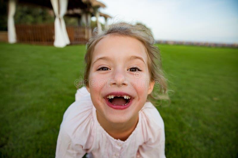 Menina saudável bonito que encontra-se no gramado verde, sorrindo felizmente imagem de stock royalty free