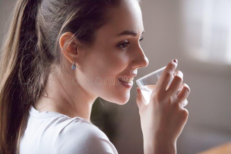 Menina saudável feliz que guarda a água de vidro da bebida ainda imagem de stock royalty free