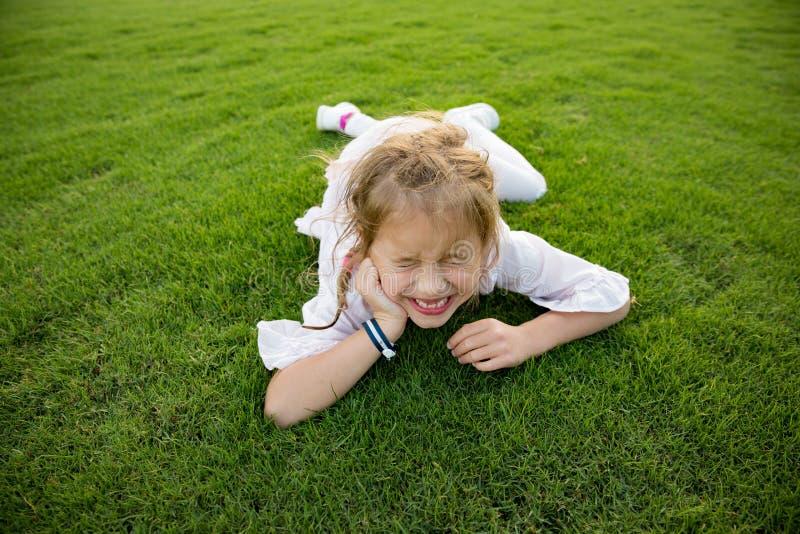 Menina saud?vel bonito que encontra-se no gramado verde, sorrindo felizmente imagem de stock royalty free