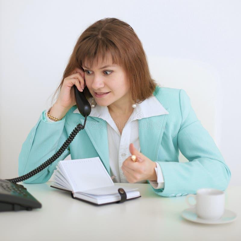 Menina - a secretária fala emocionalmente no telefone imagem de stock