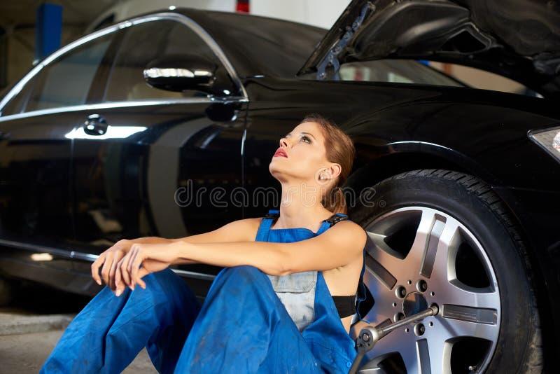 Menina sedutor perto de um carro preto na garagem do reparo fotos de stock