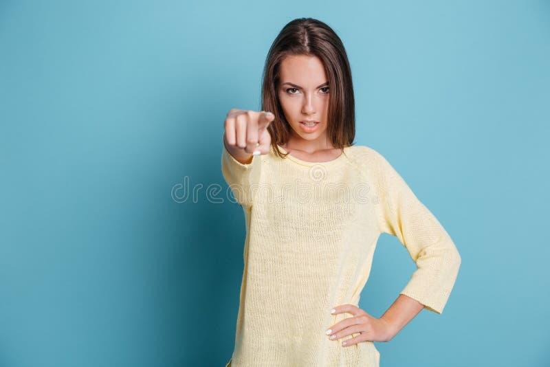 Menina segura bonita que aponta o dedo na câmera sobre o fundo azul fotografia de stock