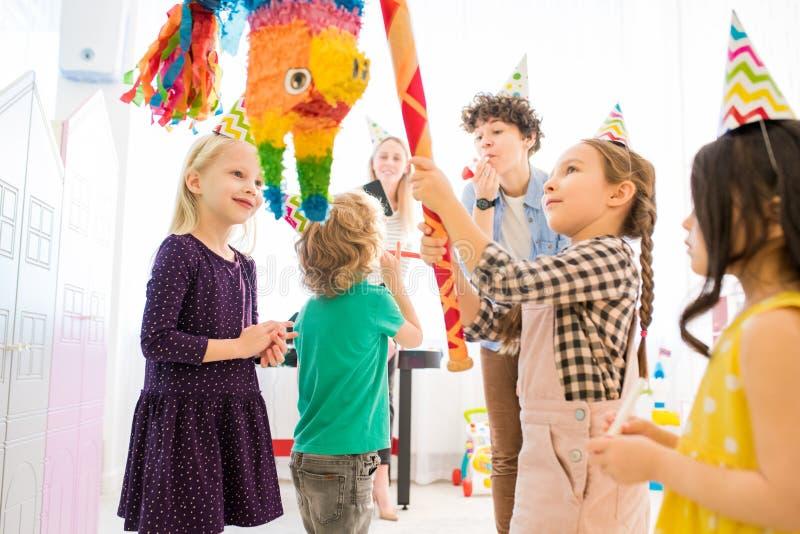 Menina segura que bate o pinata colorido na celebração das crianças fotografia de stock royalty free