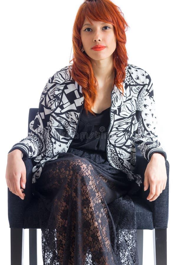 A menina segura senta-se na cadeira confortável e veste-se o preto e o whi fotografia de stock
