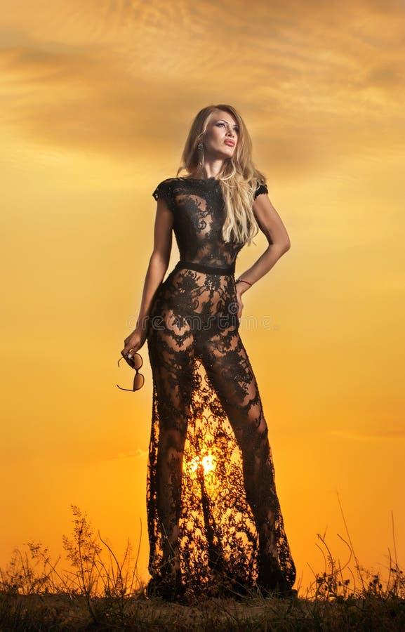 Menina sensual com o sol que aumenta atrás dela fotos de stock royalty free