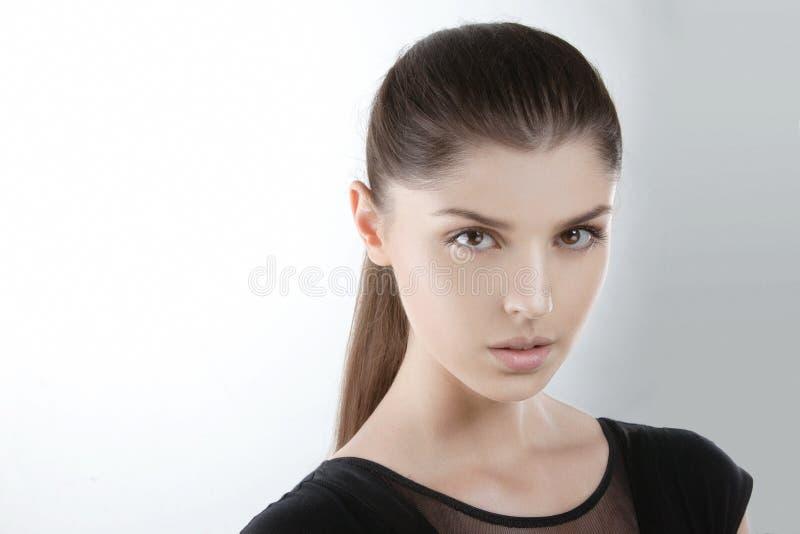 Menina sensual no vestido preto, com o cabelo apertado, olhando a câmera, sobre o fundo branco claro Cosm?ticos Copie o espa?o fotos de stock