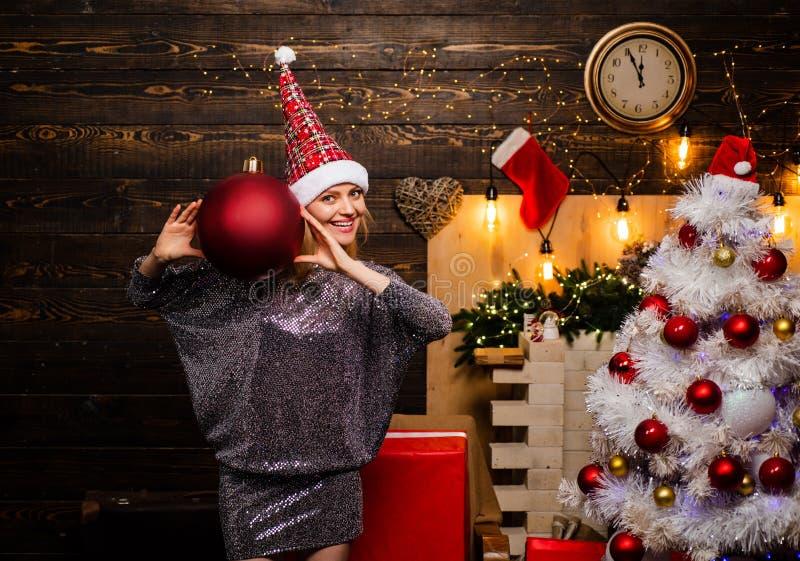 Menina sensual para o Natal Jovem mulher bonito com o brinquedo vermelho grande do Natal da bola Mulher feliz Natal feliz fotografia de stock royalty free