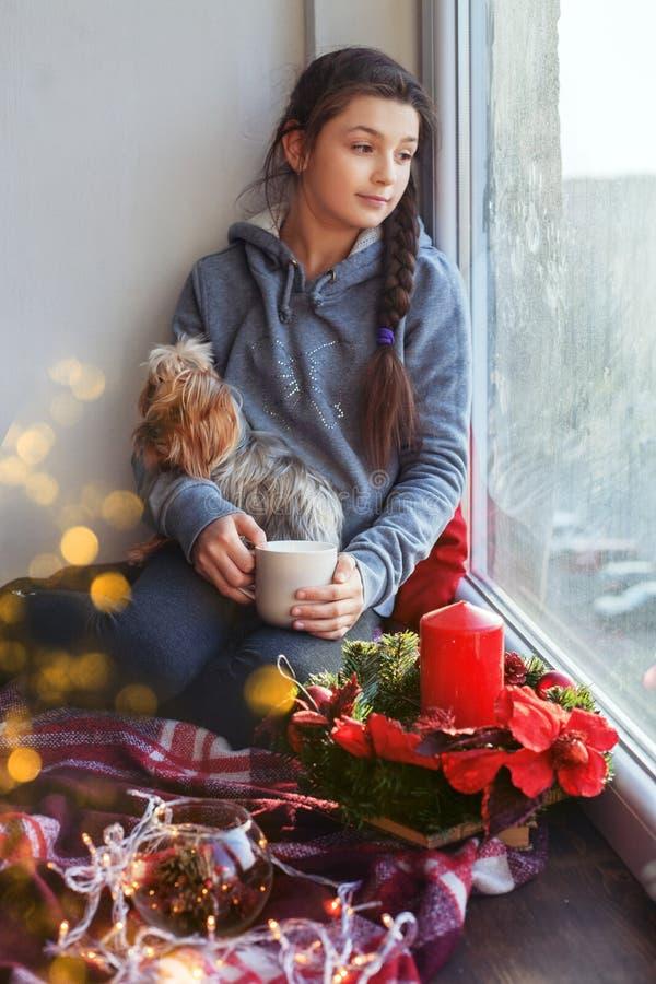 A menina senta em uma soleira com um cão um o copo do chá O conce fotos de stock royalty free