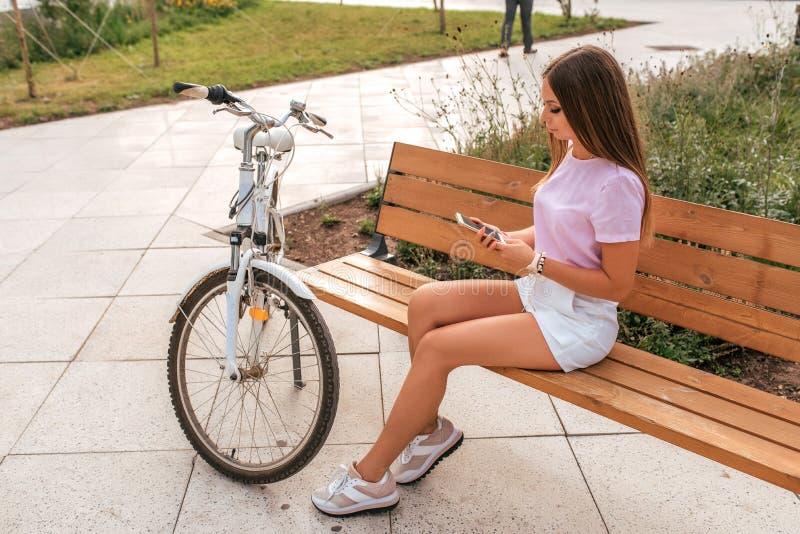 A menina senta o banco com bicicleta, cidade do ver?o Short branco da saia do t-shirt do rosa Cabelo longo L? a conversa??o no te fotos de stock