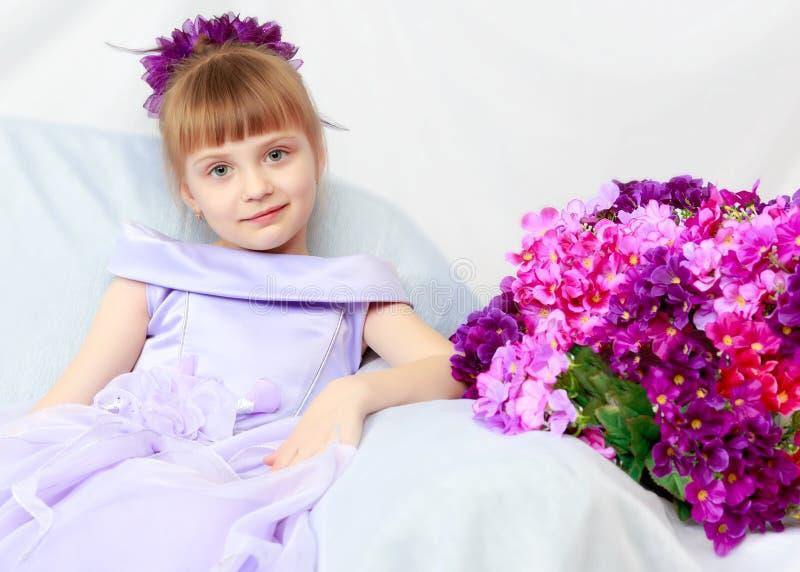 A menina senta-se ao lado de um ramalhete das flores imagens de stock