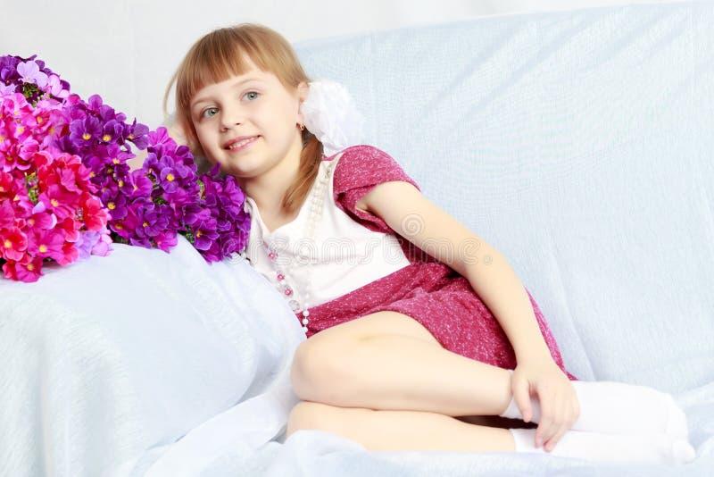 A menina senta-se ao lado de um ramalhete das flores fotos de stock royalty free