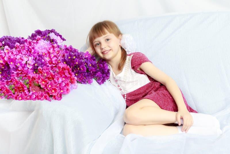 A menina senta-se ao lado de um ramalhete das flores fotografia de stock