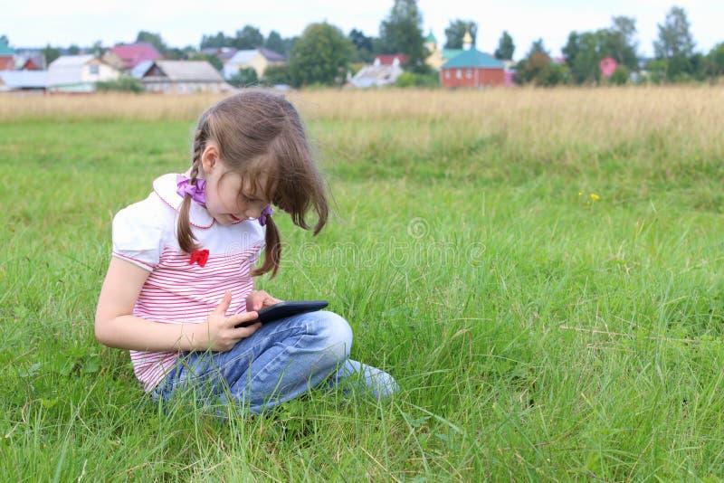 A menina senta-se e joga-se com PC da tabuleta imagem de stock