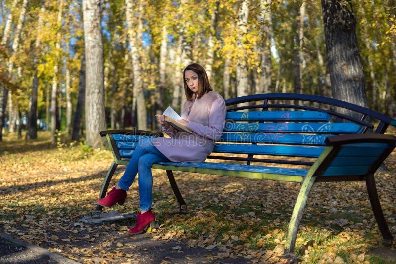A menina senta-se em um banco de parque e em guardar um livro fotos de stock royalty free