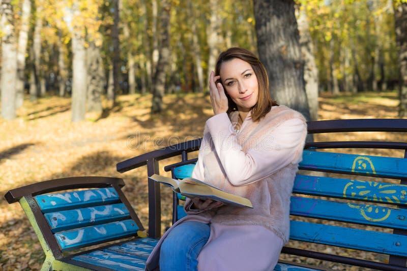 A menina senta-se em um banco e em ler um livro imagens de stock royalty free