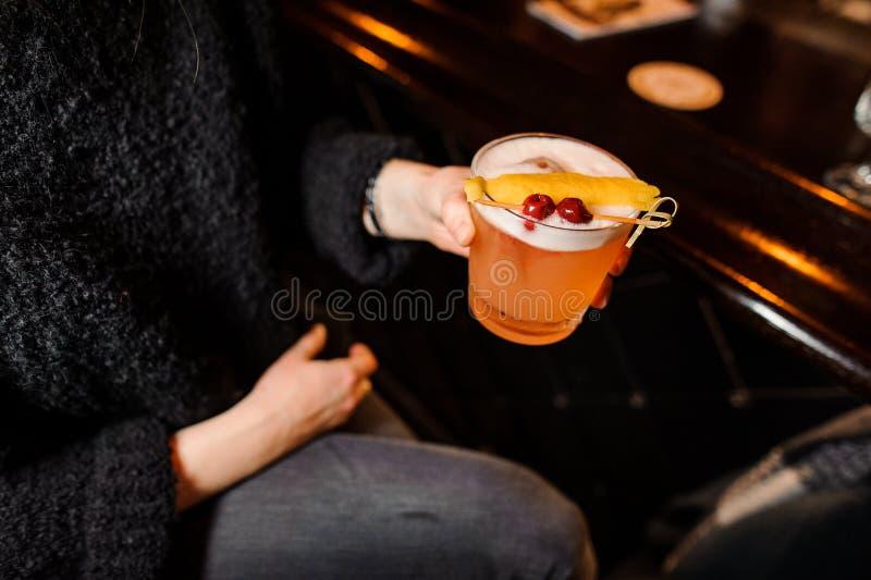 A menina senta-se em um contador da barra e guarda-se um cocktail alaranjado alcoólico na mistura ácida imagens de stock royalty free