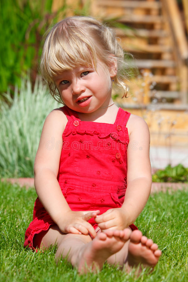A menina senta-se em um gramado imagens de stock royalty free