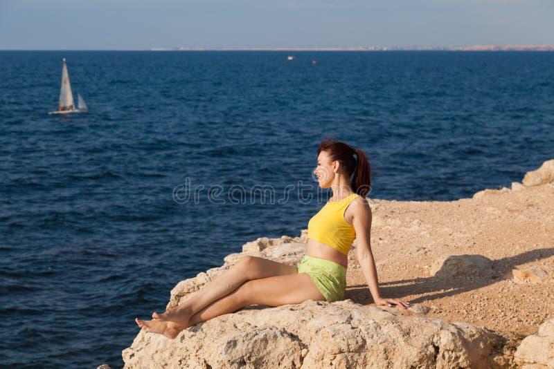 A menina senta-se em um penhasco e em olhar o mar foto de stock royalty free