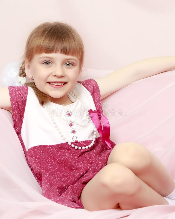A menina senta-se em um sofá cor-de-rosa foto de stock