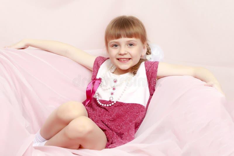 A menina senta-se em um sofá cor-de-rosa imagens de stock