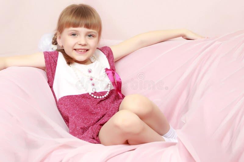 A menina senta-se em um sofá cor-de-rosa imagem de stock