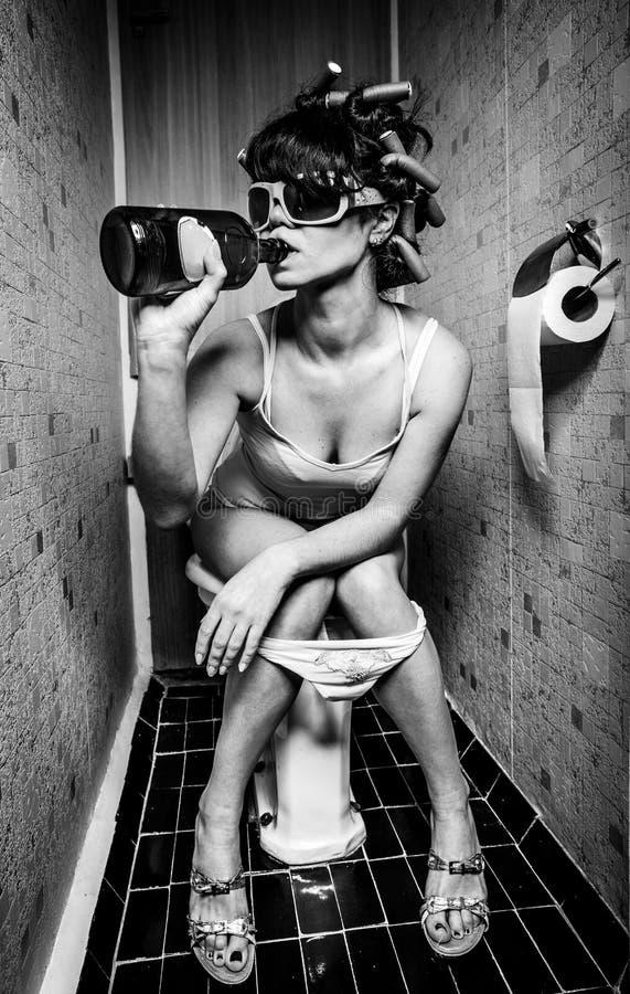 A menina senta-se em um toalete fotografia de stock