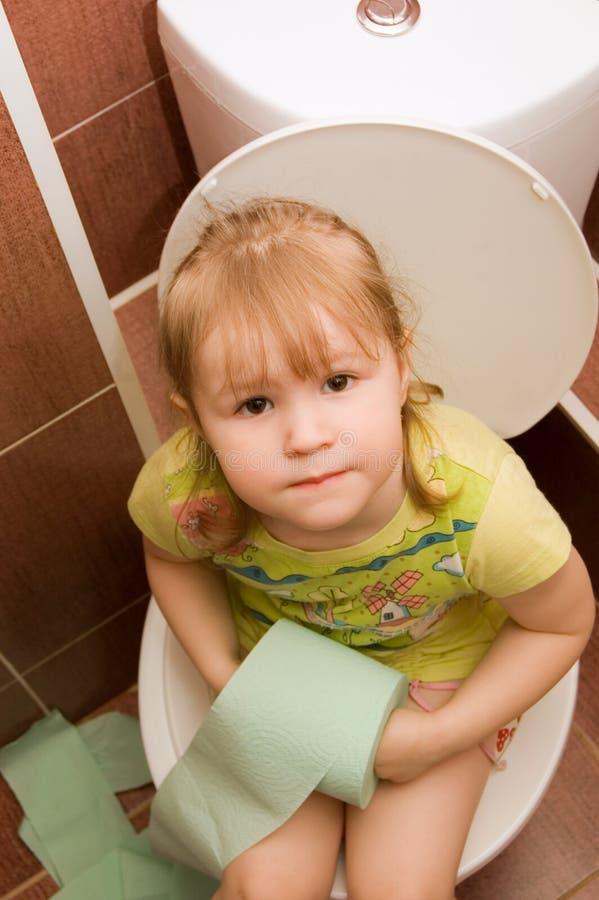 A menina senta-se em uma bacia de toalete fotografia de stock royalty free